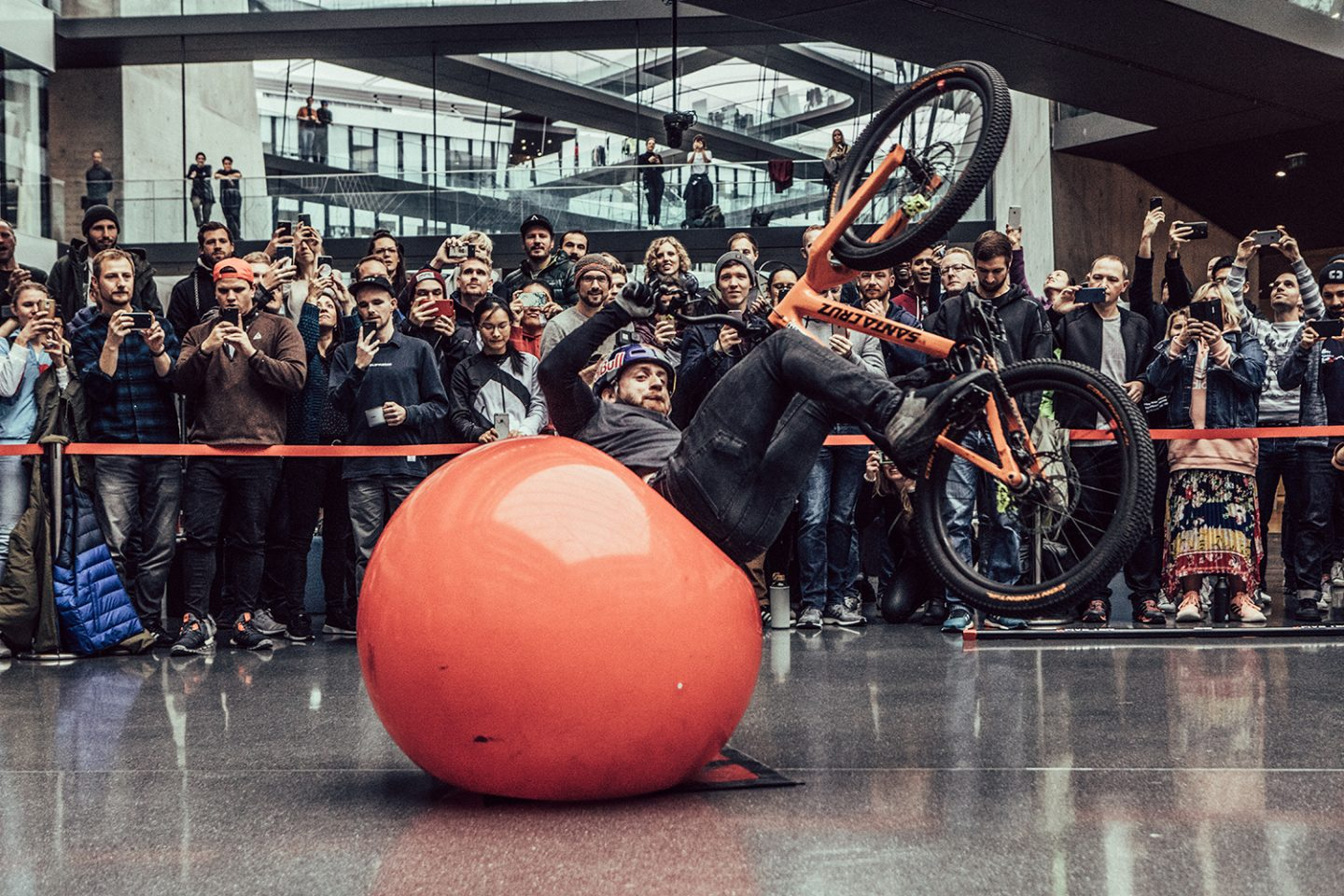 Mountainbike pro Danny Mac Askill is performing a trick on a ball with his bike at the adidas headquarter