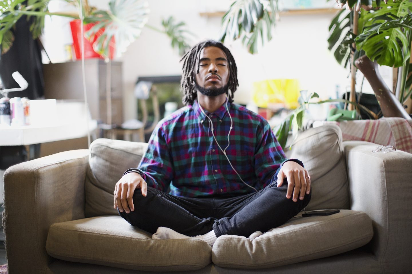 Serene young man listens to a podcast with headphones on apartment sofa | Listen to podcasts