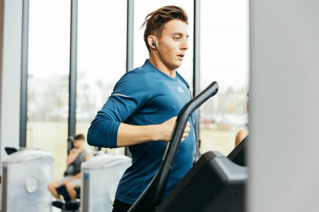 Business athlete who is running on a treadmill listening to podcasts | Listen to podacsts