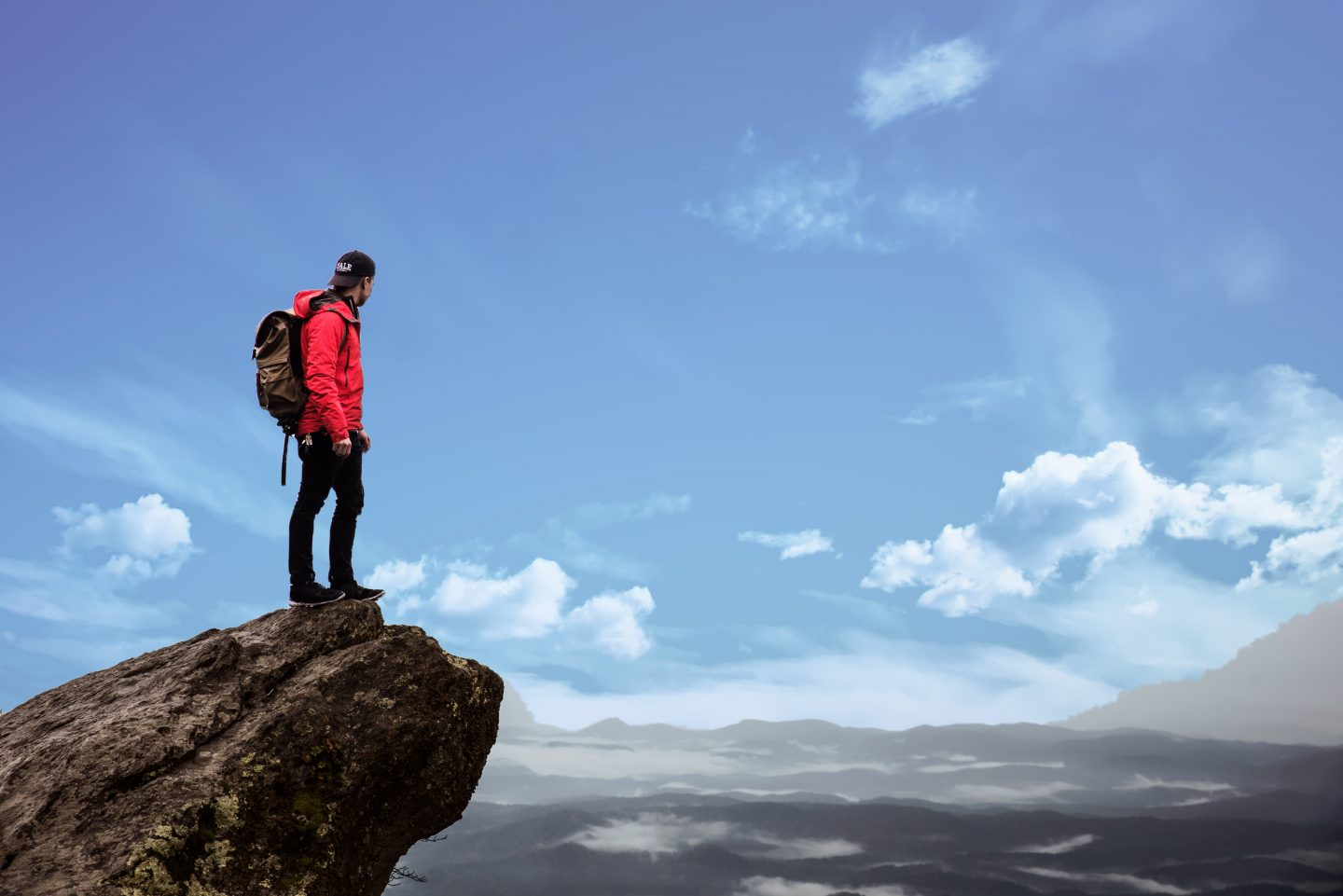 A man standing on a cliff gazing into the distance. holiday, disconnect on vacation, work, detox