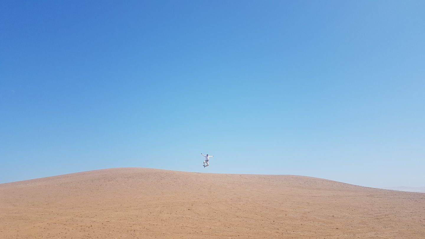 A man jumping in the desert. disconnect on vacation, holiday, work, detox