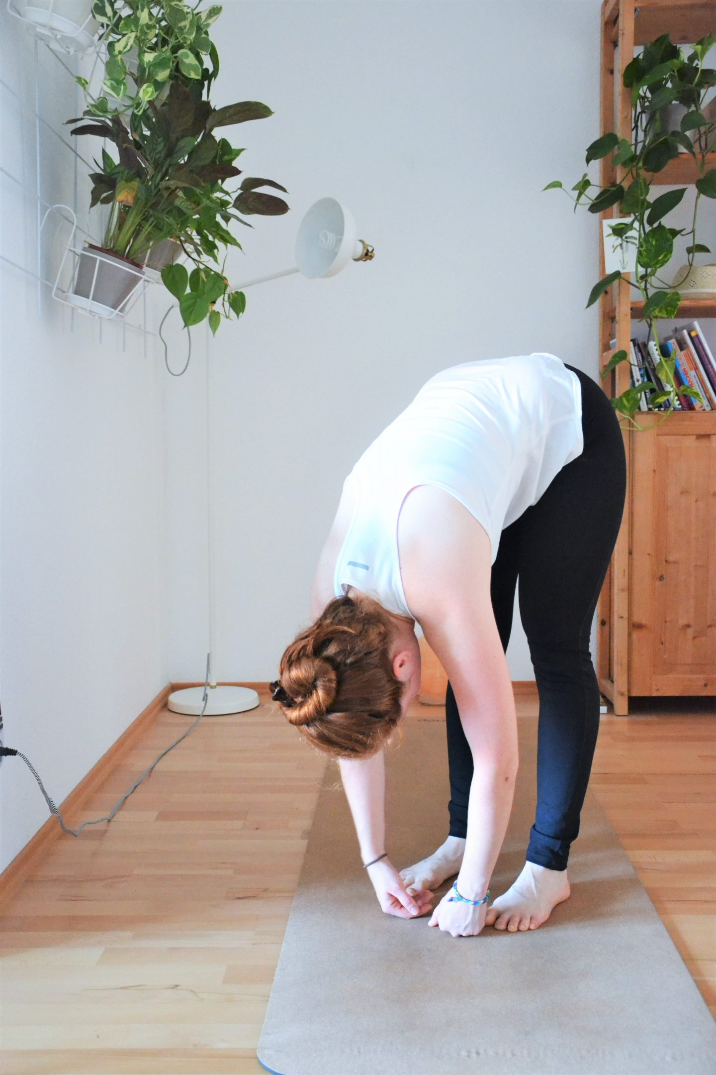 Woman practicing standing forward bend. Focus, yoga, GameplanA