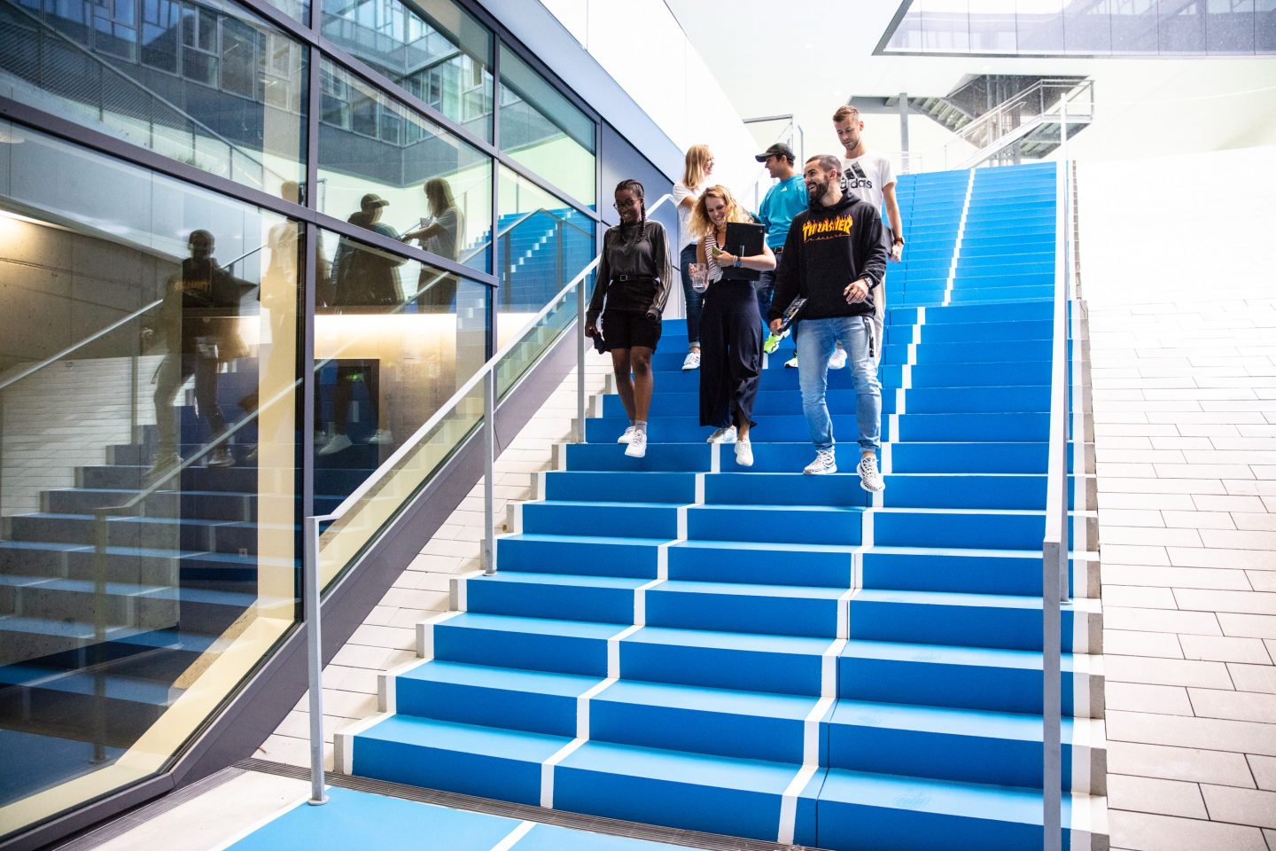 adidas employees at MyArena walking down staircase for walking meetings showing the workplace culture at adidas with collaboration