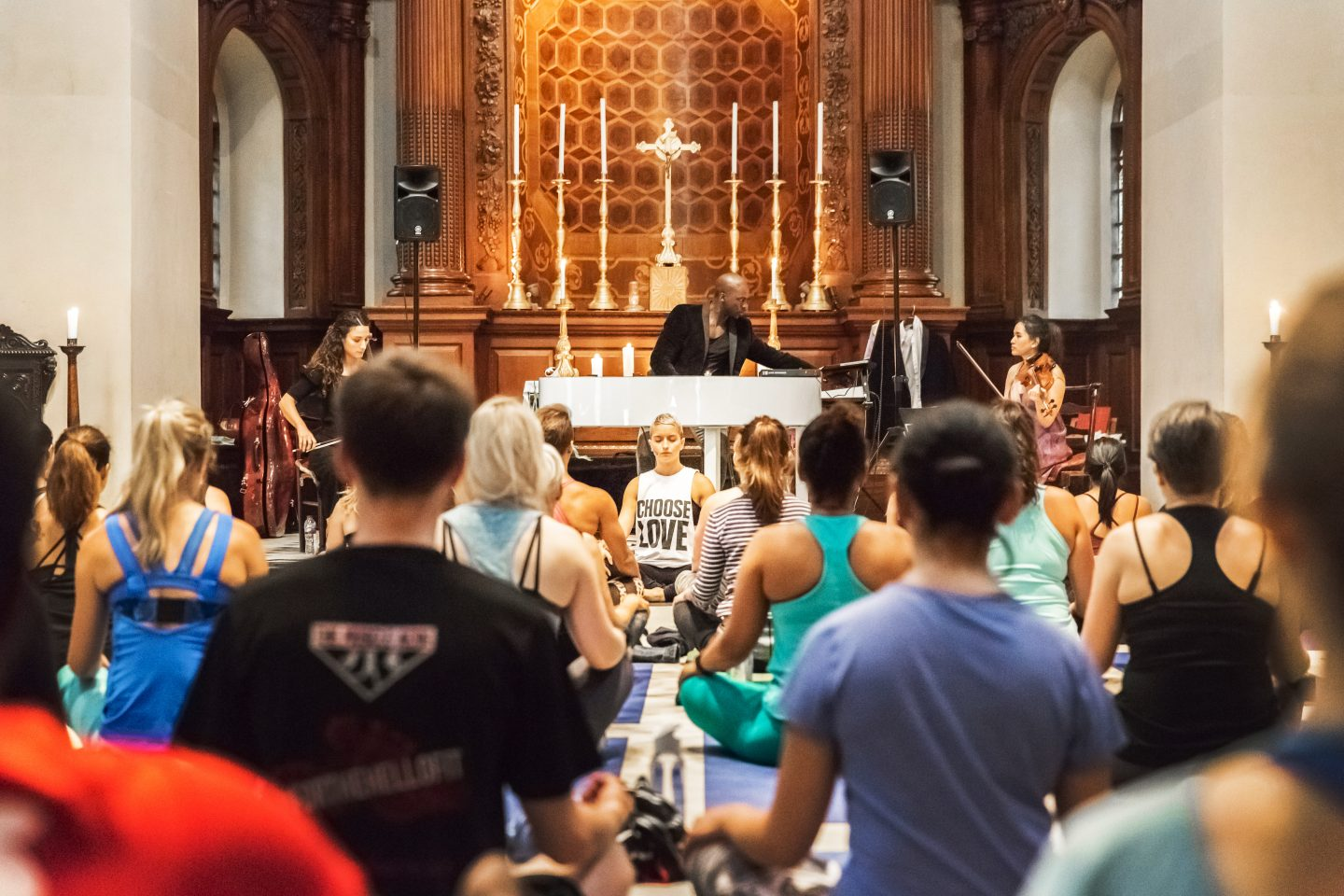 People sit crossed-legged on yoga mats in a beautiful church with a live orchestra playing music. Wellness, Gameplan A.