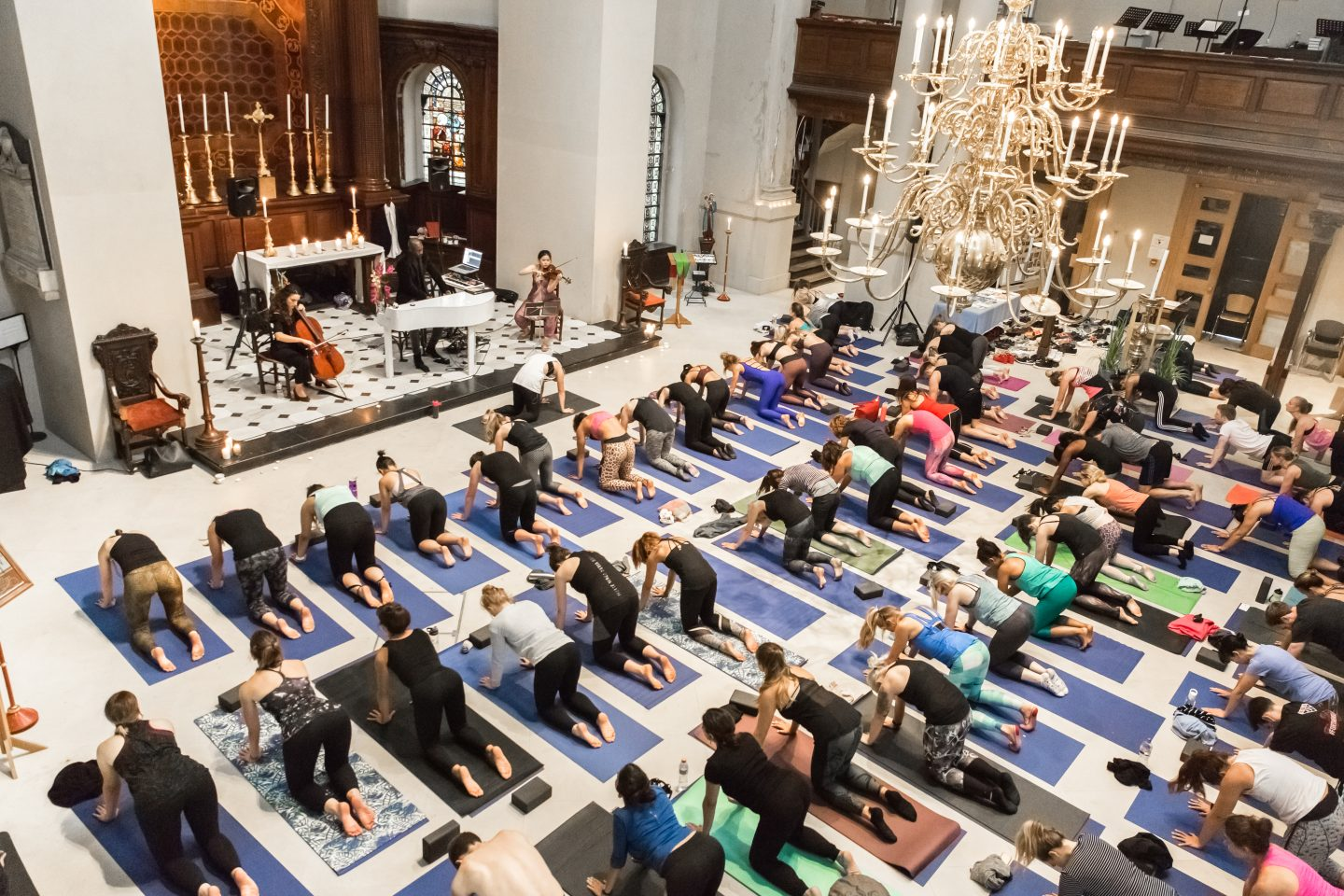 A beautiful church is filled with rows of people doing yoga on mats, accompanied by a live orchestra. Wellness, Gameplan A.