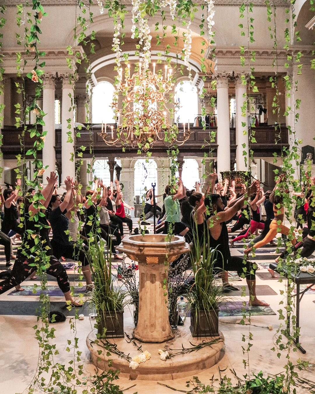 In a beautiful church a cascade of green vines hangs in front of an ornate font, whilst people do yoga in the background. Wellnerss, Gameplan A.