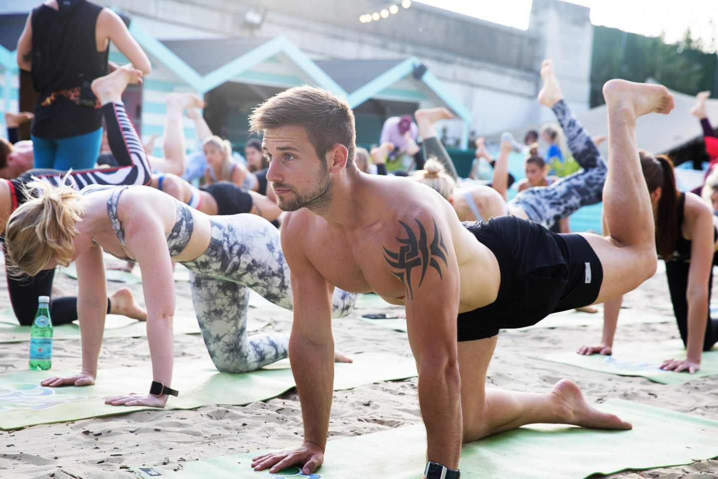 An athletic looking man on a sandy beach pulls a yoga pose on all-fours, surrounded by other people doing yoga. Wellness, Gameplan A.