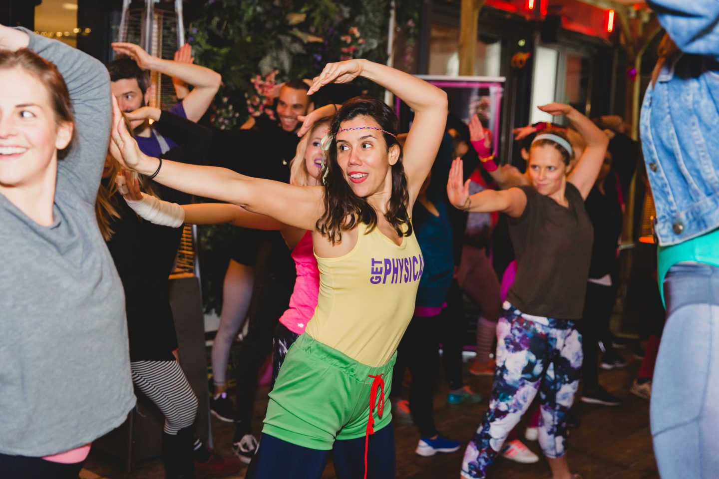 A woman dressed in retro 80s fitness clothes dances with her hands in the air. Wellness, Gameplan A.