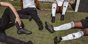Football team wearing adidas boots sitting on the pitch -Coaching Teams