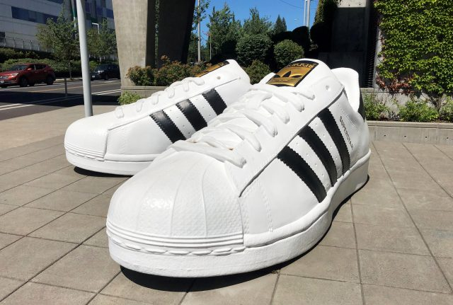 A pair of giant adidas Superstar sneakers standing on the ground. team, success, work, GamePlan A