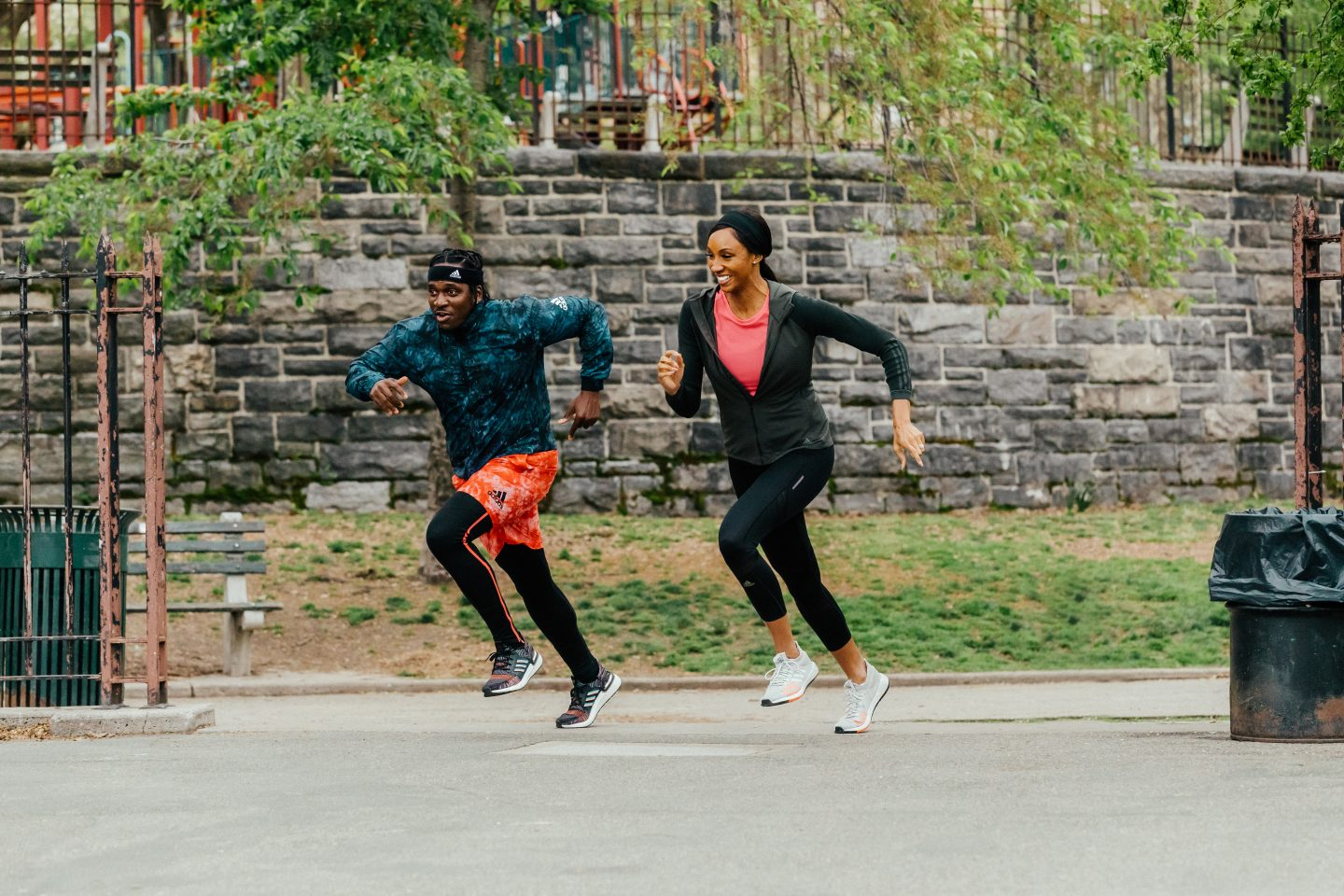 Maria Taylor and Pusha T sprint side by side in a park.