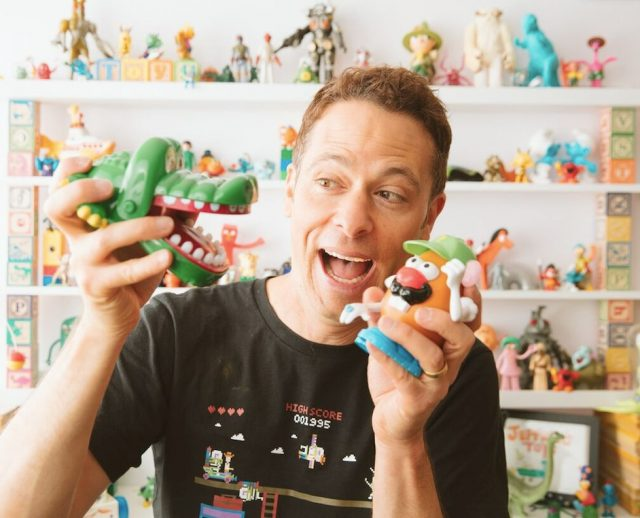 Matthew Luhn plays with figurines from the toy story film franchise.
