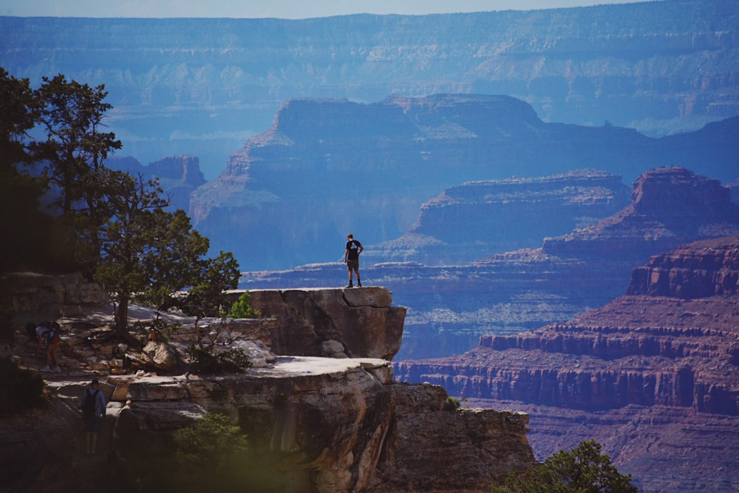 Eric Tobin stands on top of a rock looking down into the Grand Canyon.