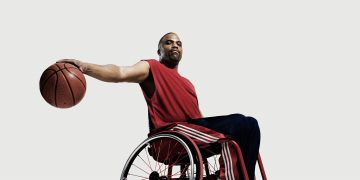 Wheelchair basketball player holds basketball.