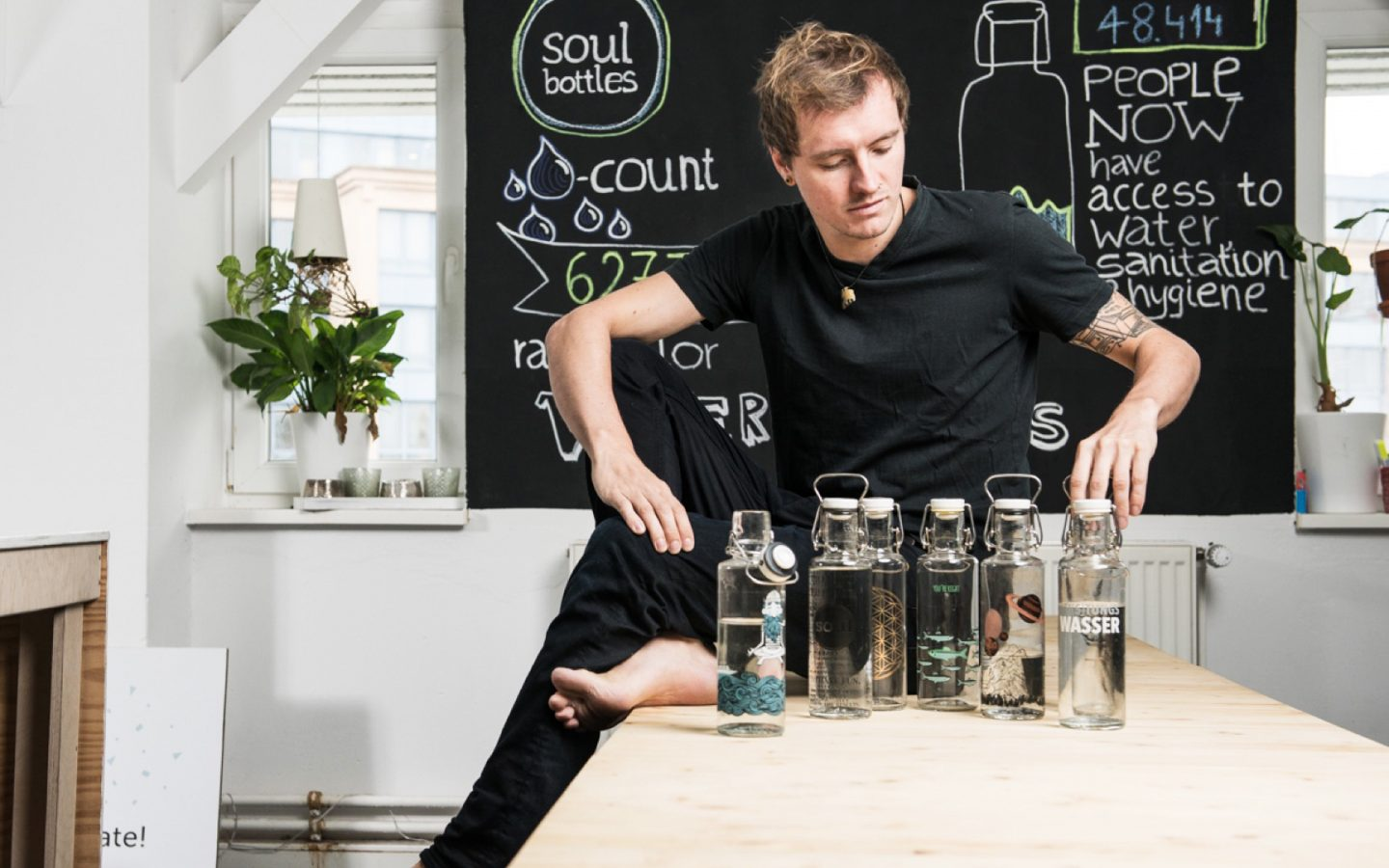 Co-founder and CEO of soulbottles sits on a table with a selection of glass bottles.