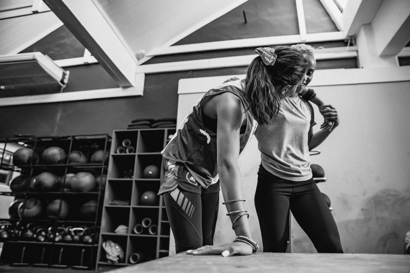Two women standing in a gym room, one leaning on the other.