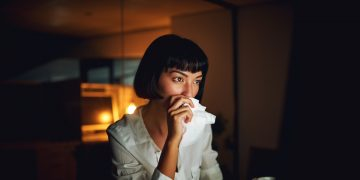 Shot of a young businesswoman blowing her nose during a late night at work