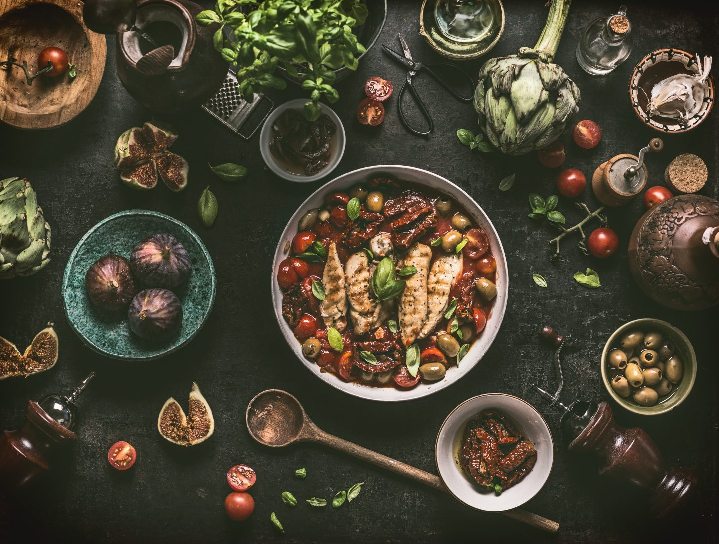 Grilled chicken breast with Mediterranean sauce in cooking pan and ingredients: tomatoes, artichokes, olives, sun-dried tomatoes,figs, anchovies, fresh seasoning herbs and spices on dark rustic table with vintage kitchen utensils , top view.