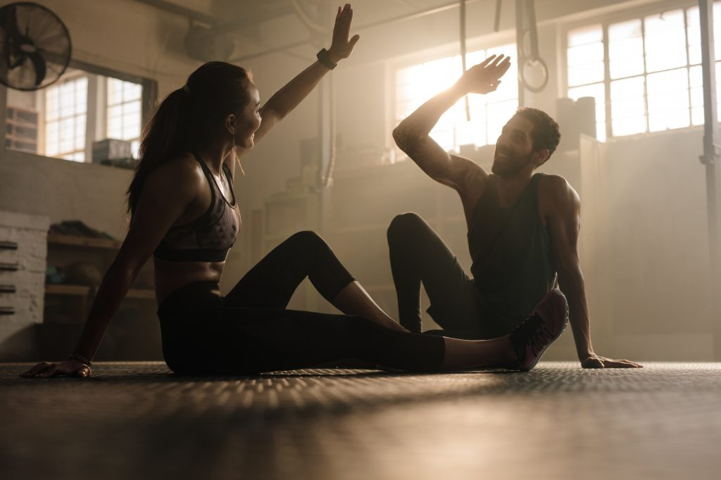 Man and woman sitting in sports clothes on the floor and giving each other a high five. motivate, athlete mindset, self-improvement, success at work, GamePlan A