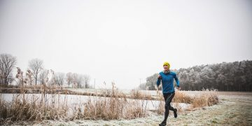 man running next to lake winter last run of the year