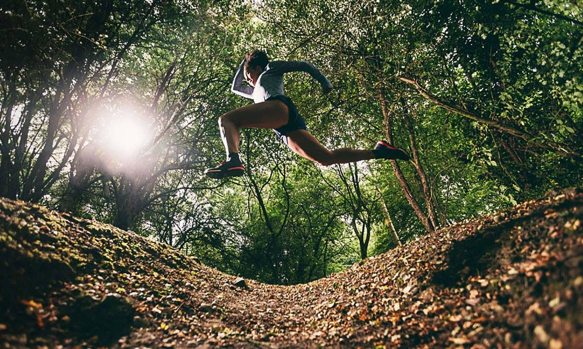 woman jumping over obstacle while running in the forest how to clear the hurdle