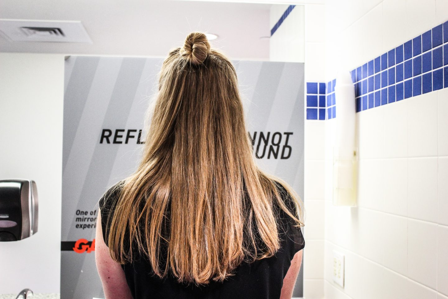 girl from the back looking into a covered mirror, mirror-free, girl standing in the restroom