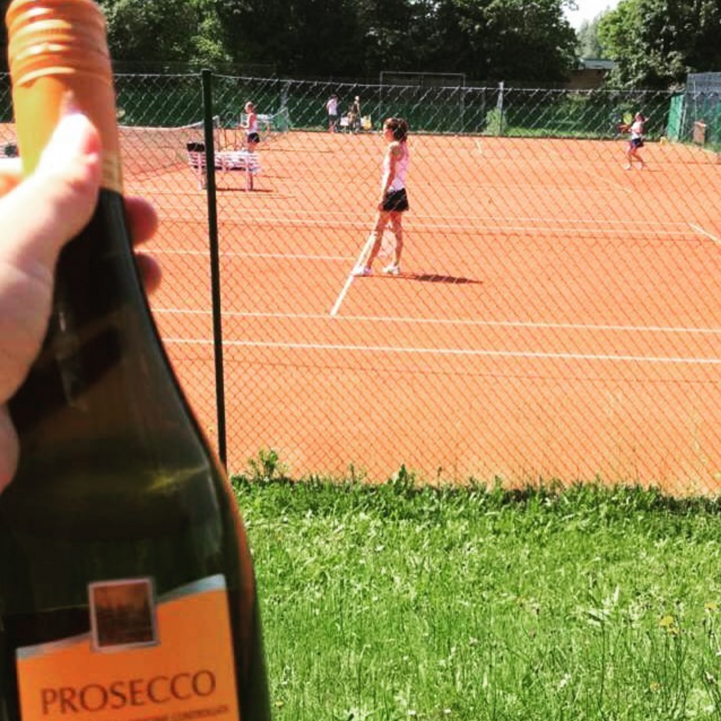 Prosecco in in front of a tennis court