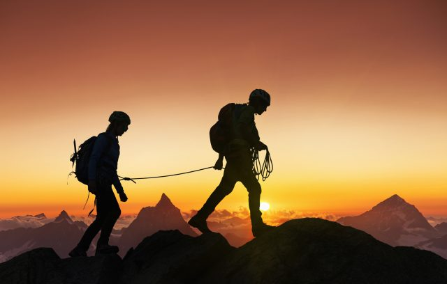 Silhouette of a couple of climbers on a mountain ridge at sunset