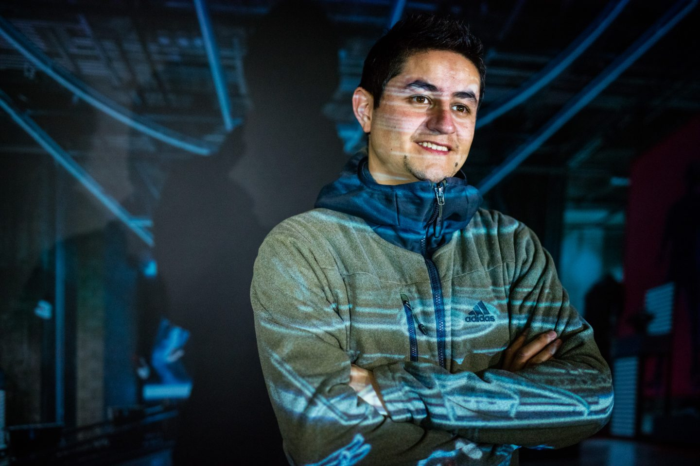 Man with crossed arms smiling with a projection behind him
