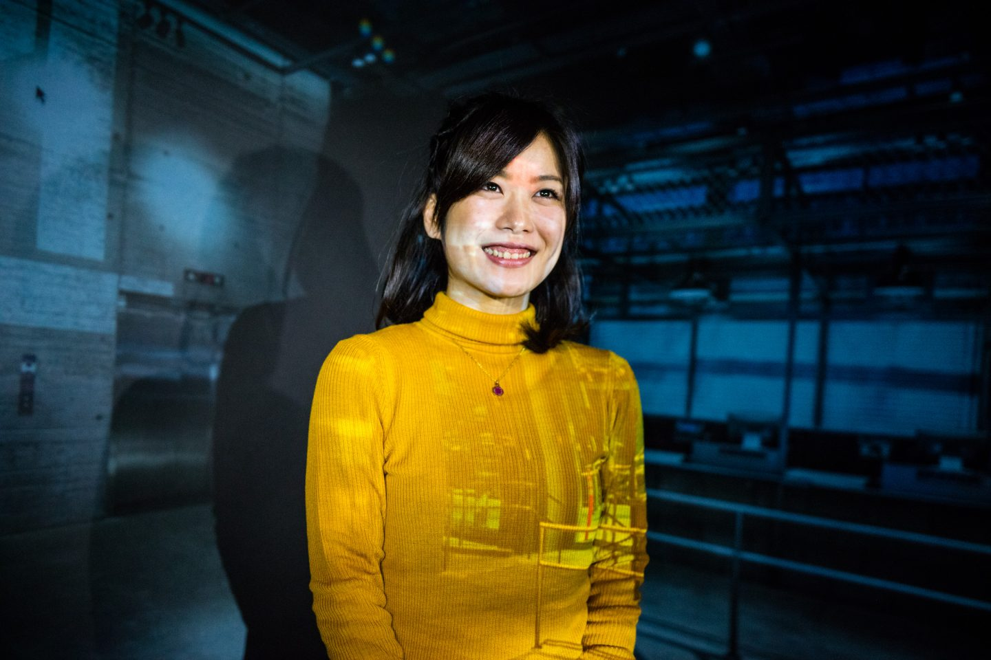 Woman smiling with a projection behind her