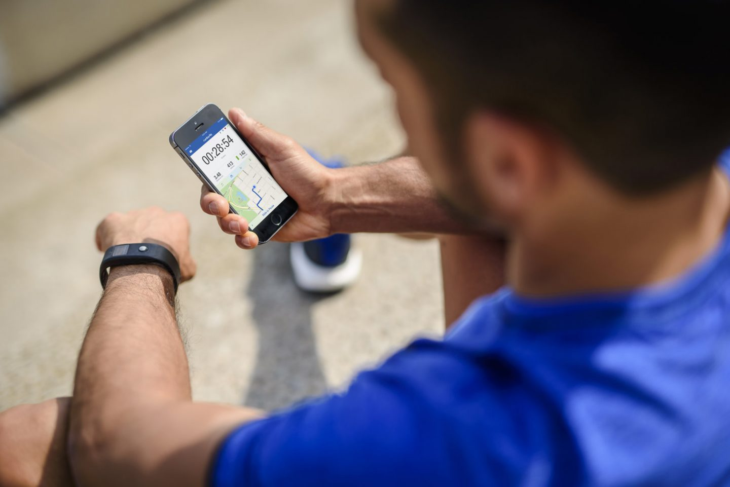 man in running clothes looking at the runtastic app on his phone