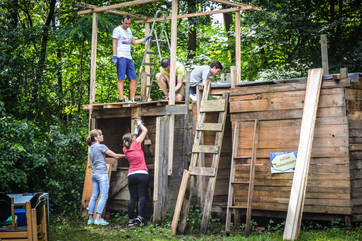 five people working on a treehouse
