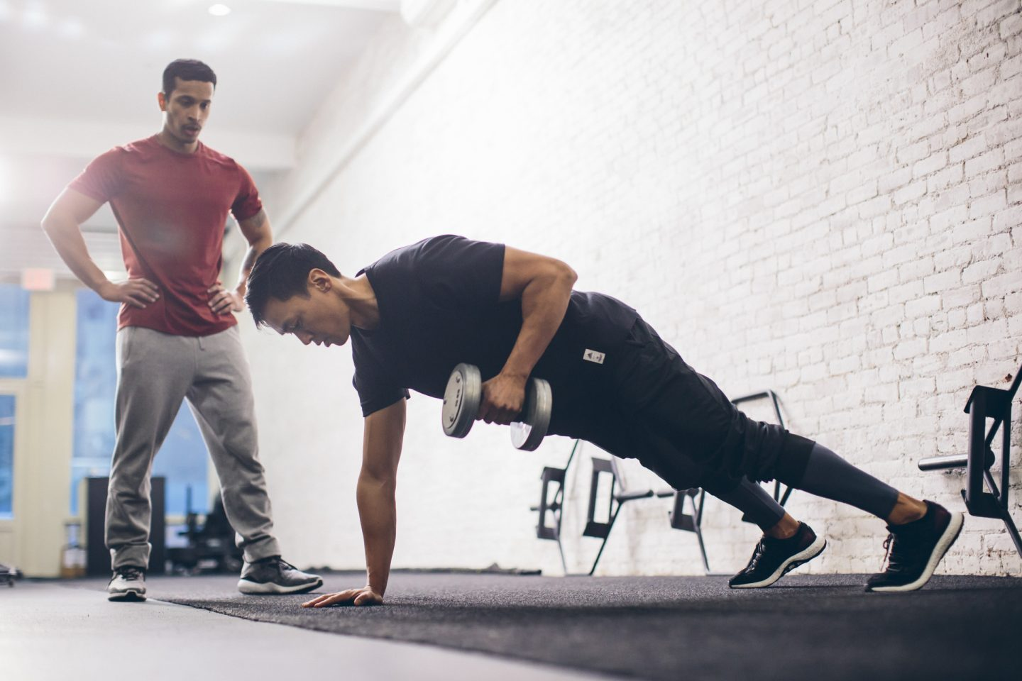 Two men working out in the gym with dumbbell. adidas partner workout rowing with dumbbell, future trends, digital, health, well-being, fitness