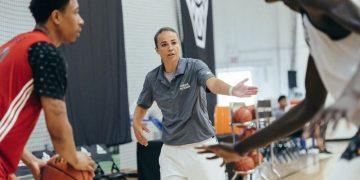 Becky Hammon coaching her player while he defends his opponent