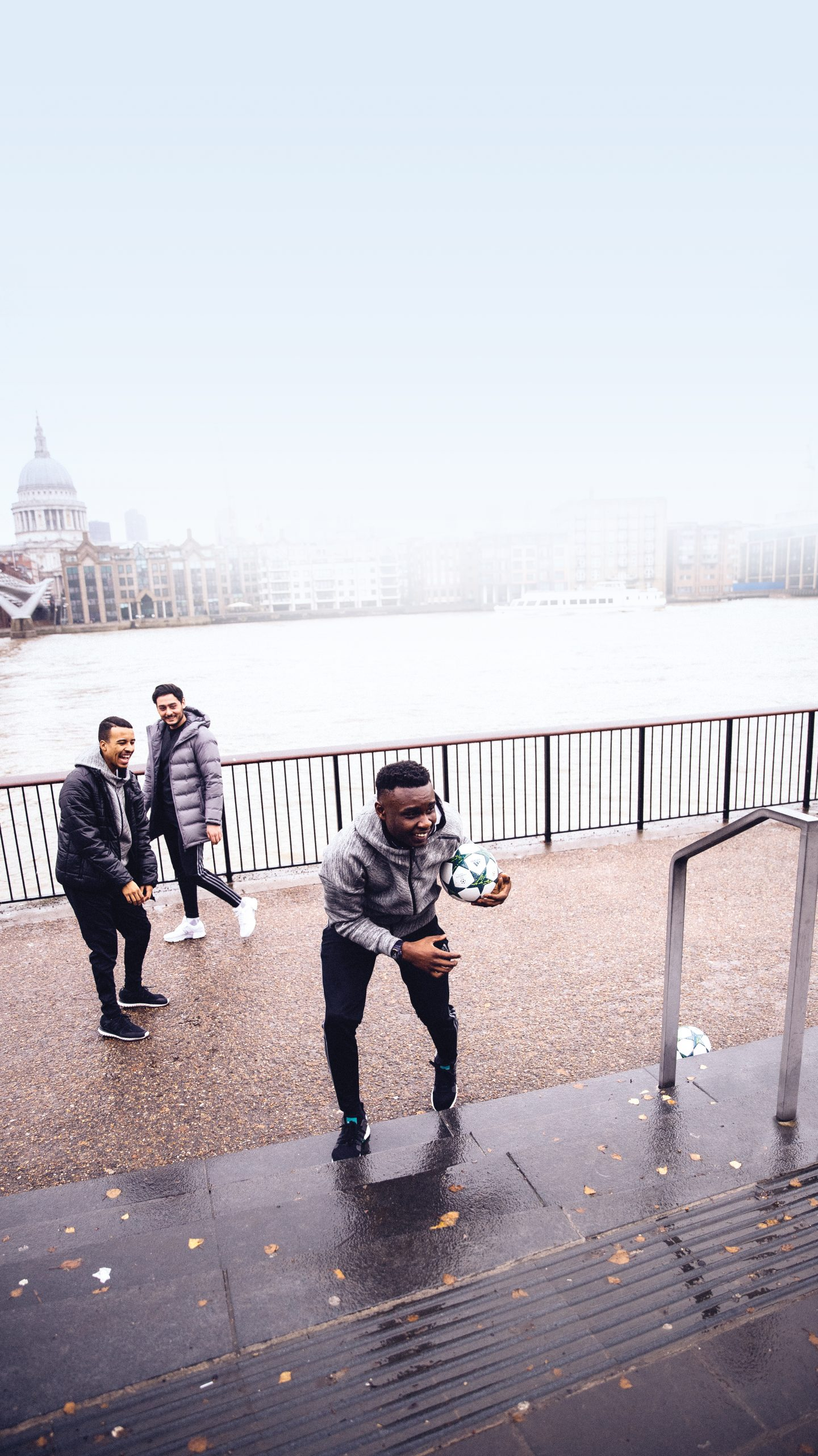 three young men playing football next to Themse London London footballers Glitch creators