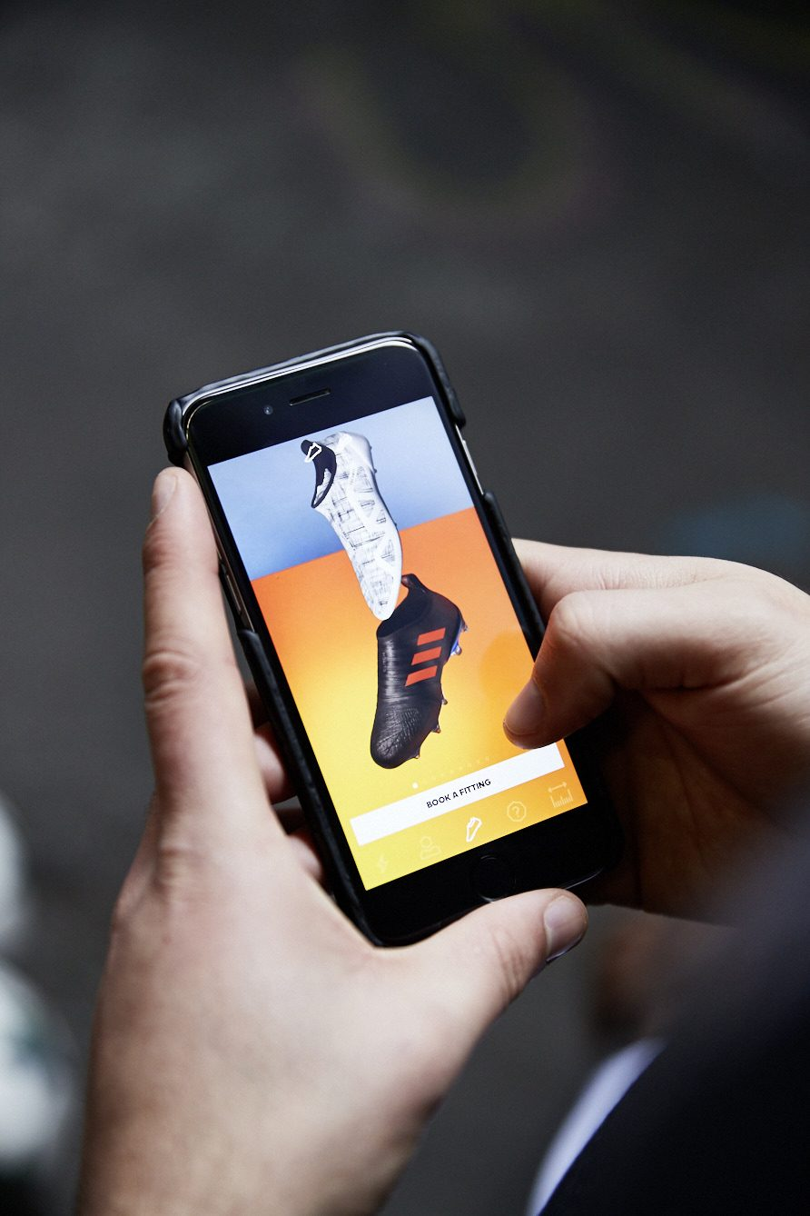 hands holding a phone showing a football boot app, adidas GLITCH football boot, app
