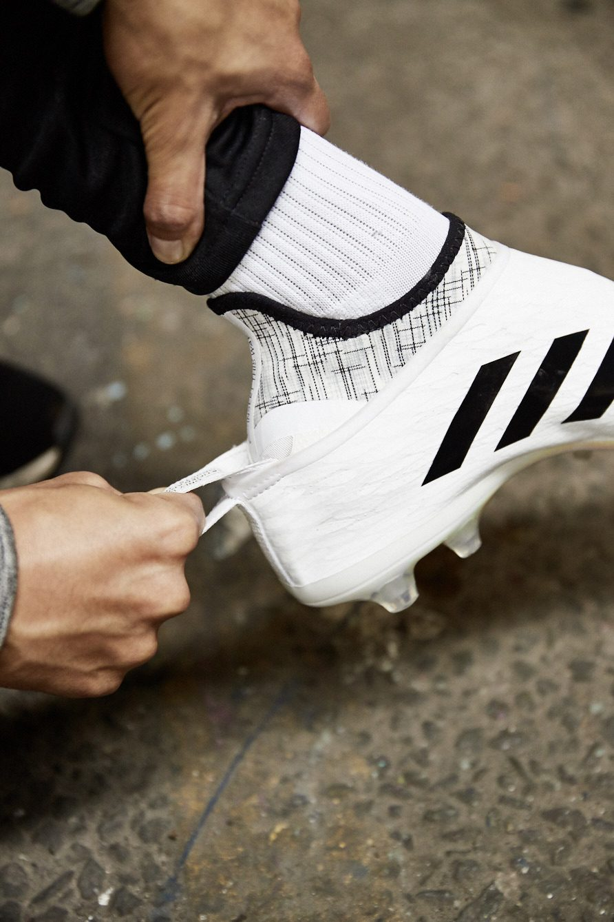 Man trying on adidas football boot GLITCH, putting on interchangeable skin