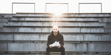 man sitting outside on stairs holding football boot how to finally start doing what you love
