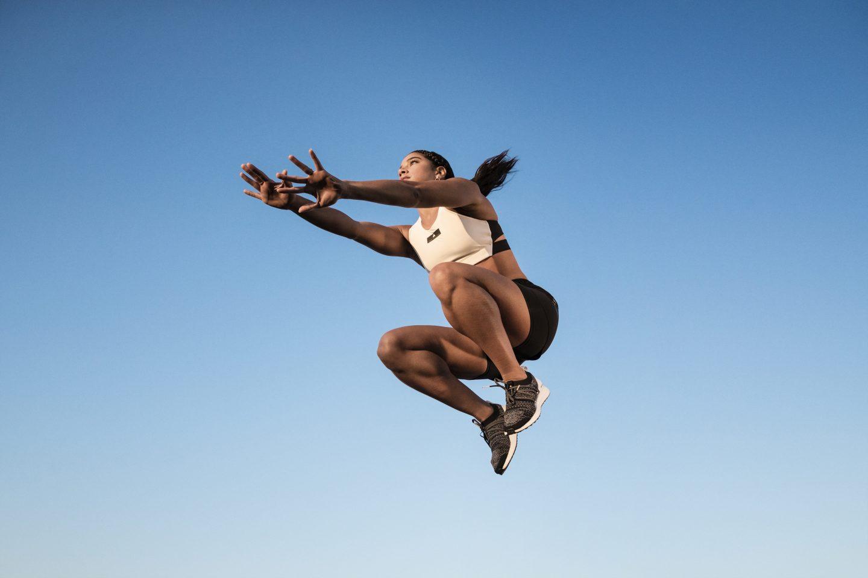 woman jumping blue sky adidas-millenial hannah bronfman