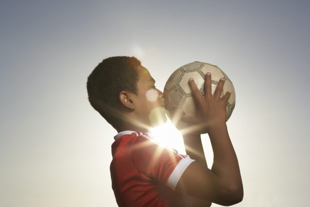 Profile of boy (12-13) kissing football falling in love with sports