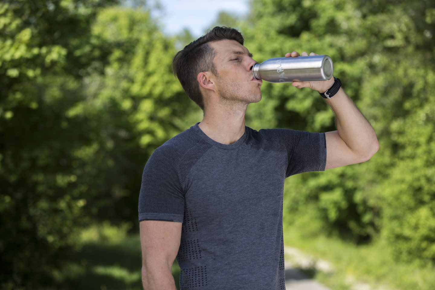 Male runner drinking out of a water bottle after workout; adidas-runtastic-parley-running-for-the-oceans-pausing-drinking-bottle-Florian-Gschwandtner