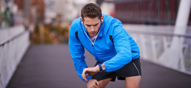 Man looking at his watch wearing running gear. Time Management Productivity INC