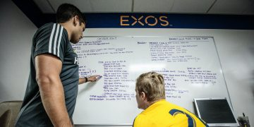 two men discussing writing on board-exos-short-term-goals-long-term-succes