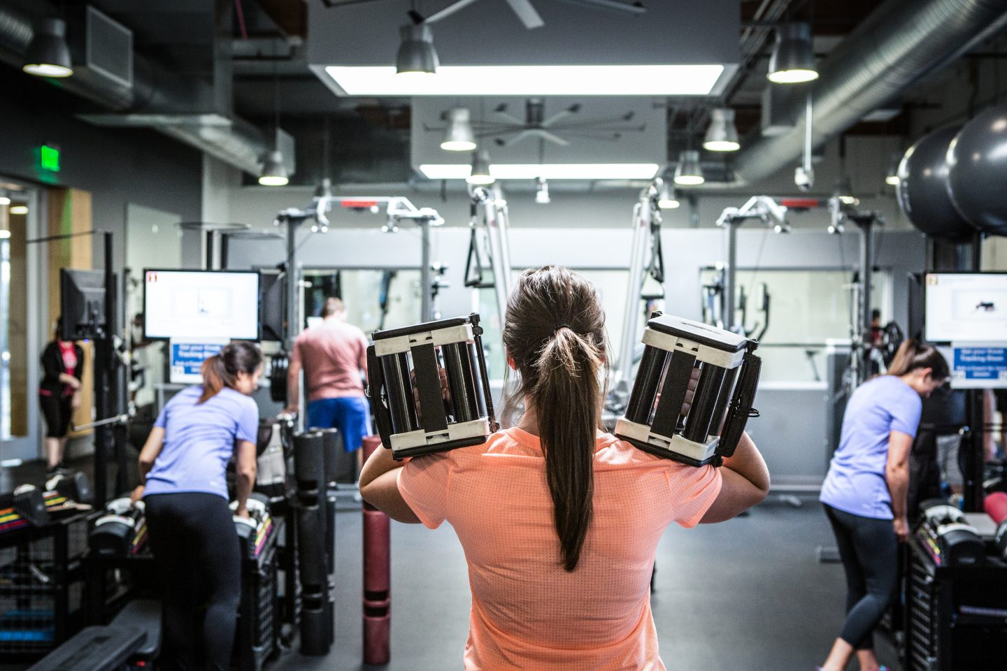 woman with powerblocks in gym-exos-short-term-goals-long-term-success