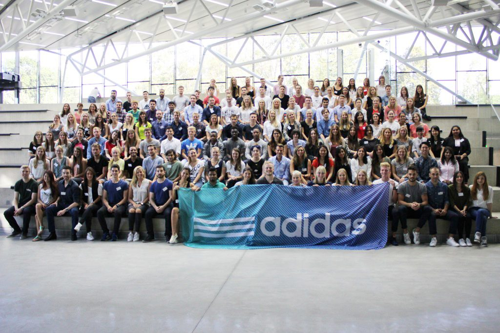 many young people sitting on stairs holding adidas flag interns at adidas