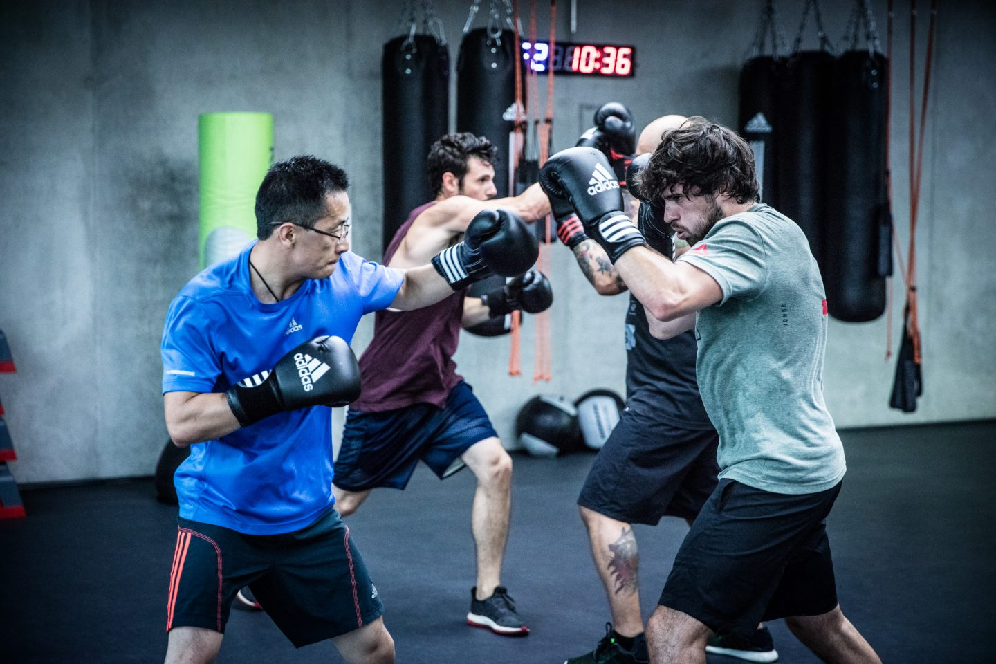 Two guys at a boxing session practice fighting with gloves on