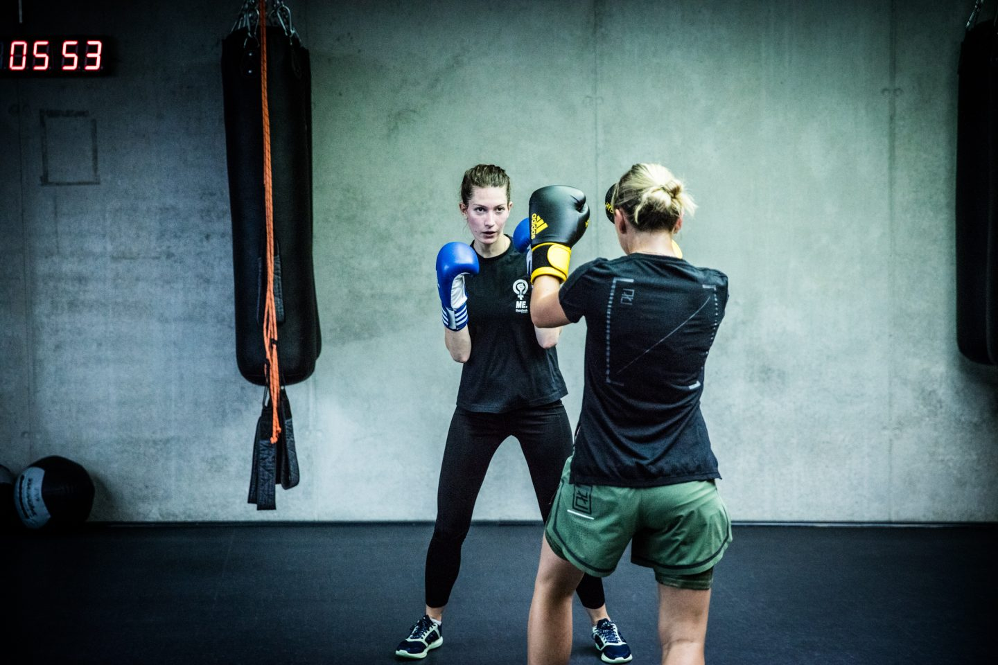 Boxing session two women practice fighting with their boxing gloves on