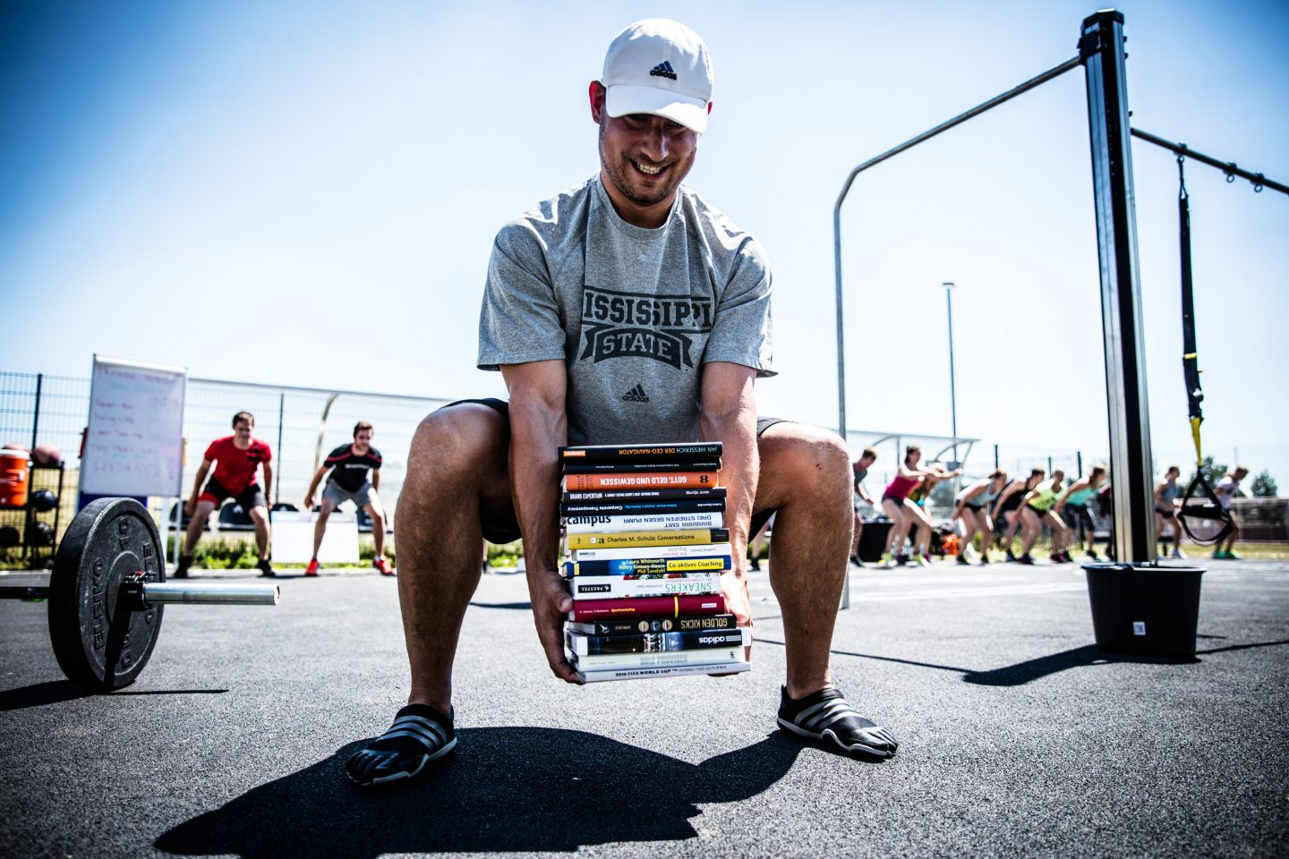 athlete lifting books during outdoor workout summer reading list for athletes at heart