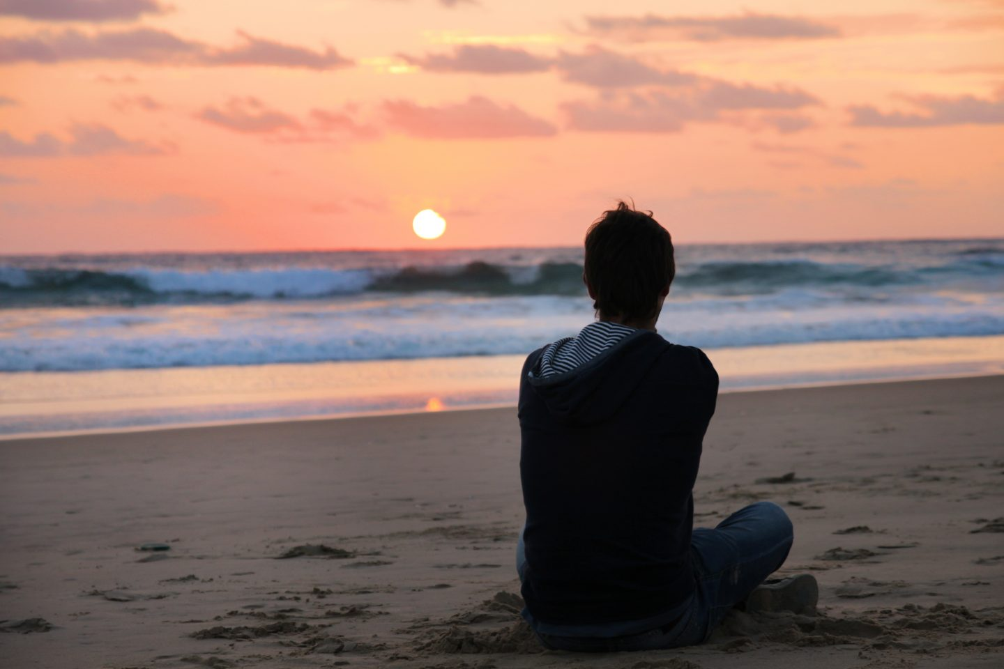 Guy sitting at the beach while watching a sunset during his holidays