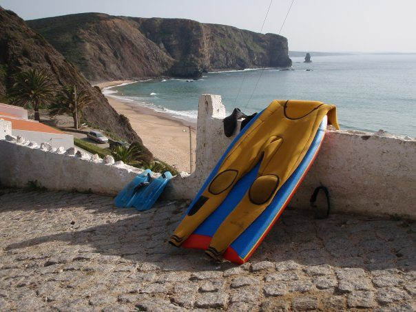 Body surf board leaning at a wall. In the background you can see a beach.